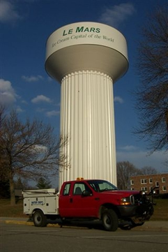 Le Mars Ice Cream Captial of the World water tower with a department truck parked in front of it and