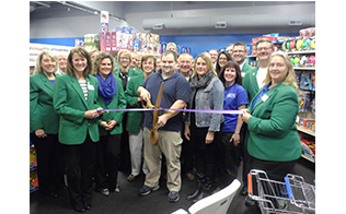 Chamber Members and a business owner with large scissors cut the ribbon at a retail store opening