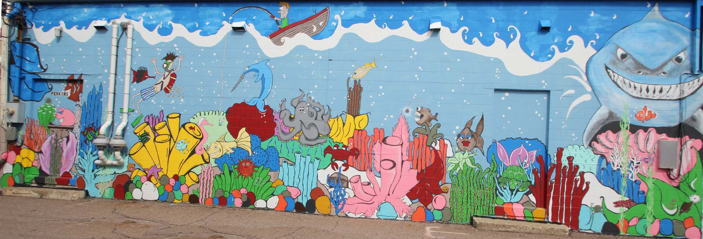 Mural of a cartoonish underwater scene, featuring fish, a scuba diver, coral, a shark, and octopus, and a guy in a boat on top with a fishing pole