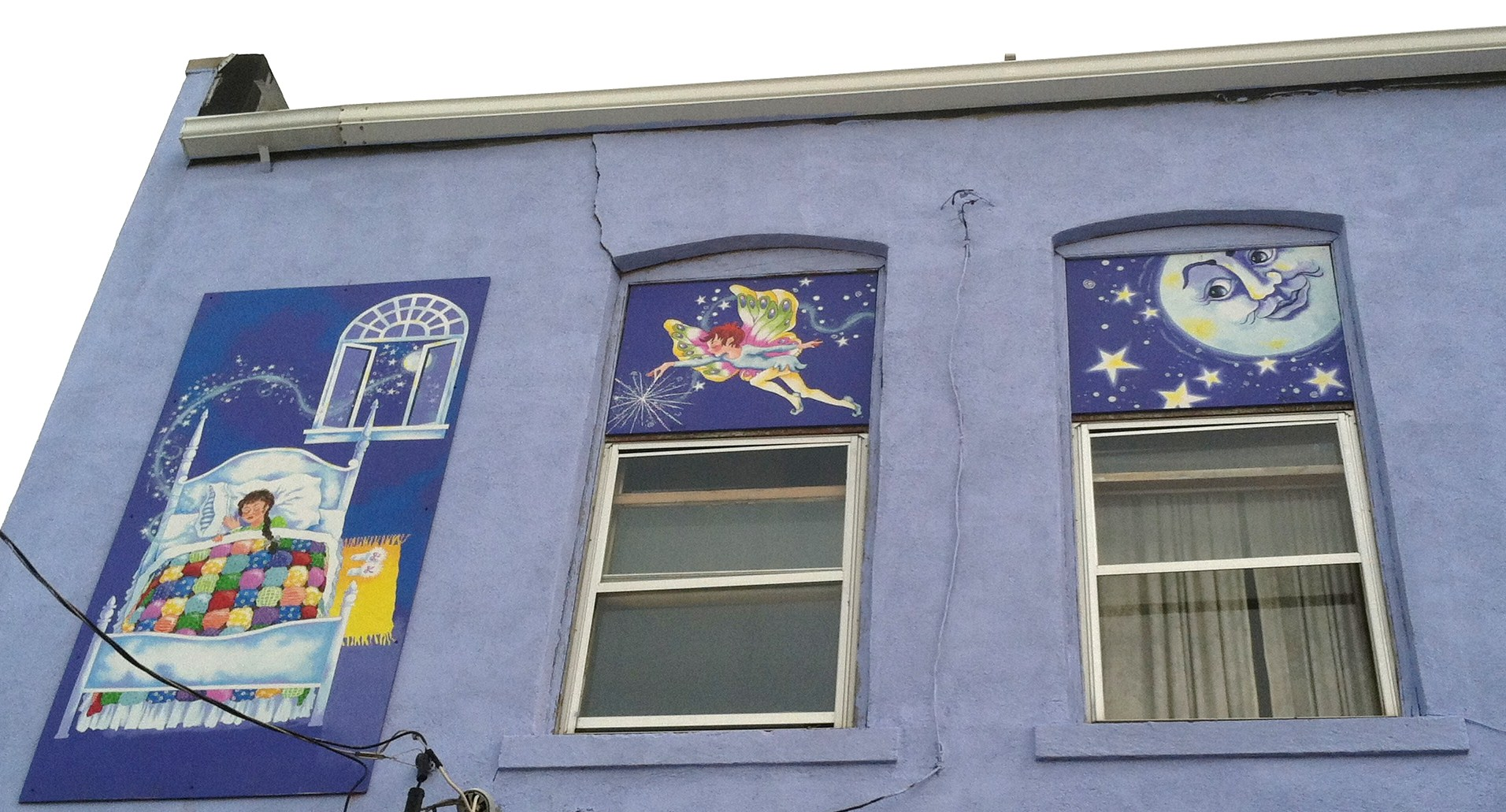 Mural on the side of a building and above windows with a little girl sleeping in a bed, a tooth fairy holding a wand, and a moon with a face looking down