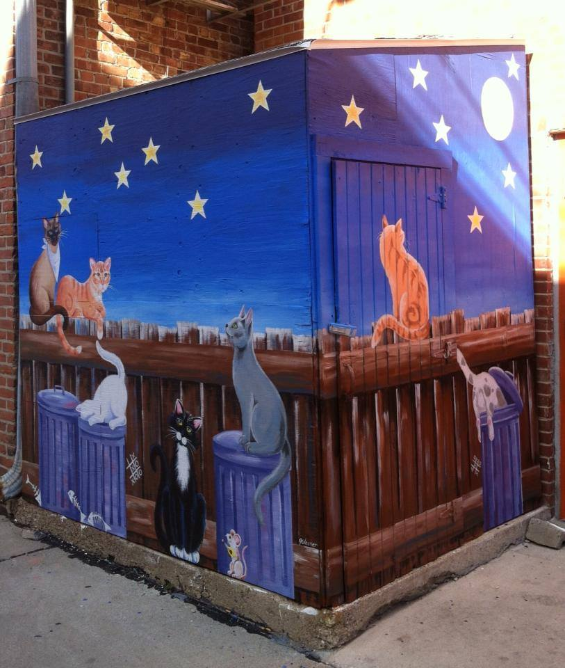Mural on an alley shed depicting cats sitting on a fence and trash cans under a starry sky