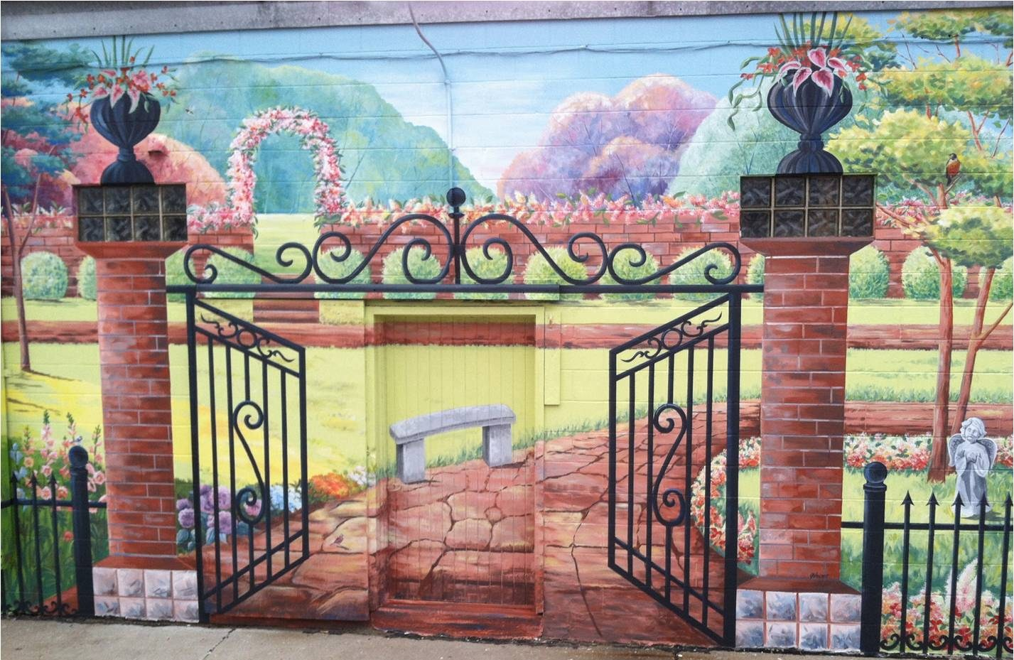 Mural of a gated entryway leading to a garden with trees, flowers, a bench, and small statues