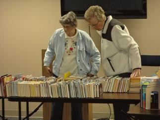 2 women browse used books at the 2013 Book Sale.