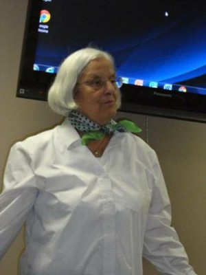Aurelia addresses the room wearing a white shirt and green scarf around her neck.