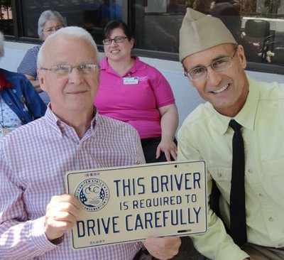 "2 men smile while one holds a licence plate that reads, ""This drive is required to drive carefully."""
