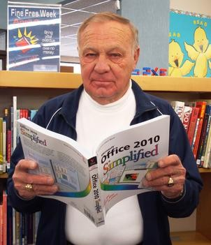 "The Mayor of Le Mars reads ""Office 2010 Simplified"" at the Library."