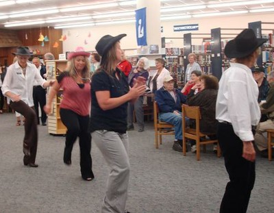 Wearing cowboy hats, women line dance at the Library.
