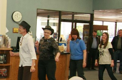 4 women smile as they participate in a line dance at the Library.