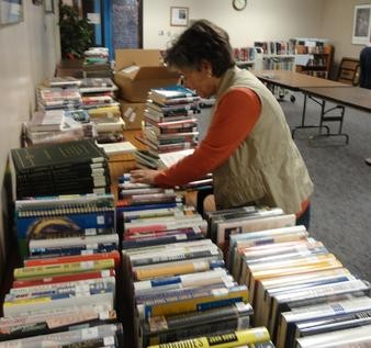 A woman sifts through used books at the 2013 Library book sale.
