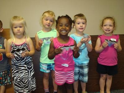 5 young children smile at the camera during the Summer Reading Program at the Library.