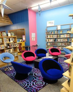 A mix of blue and pink chairs sit atop a purple spiral rug in the Teen Reading Room.