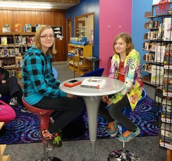2 teen girls pose with the table and chair set purchased by the Friends of the Library.